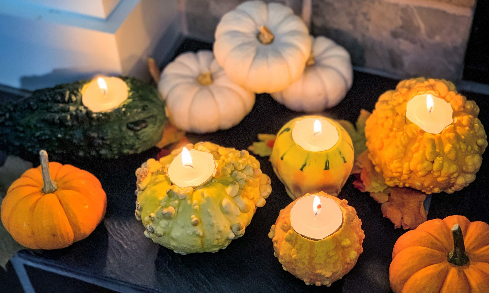 fall gourds with tea lights lit, sitting on the mantle of a fireplace