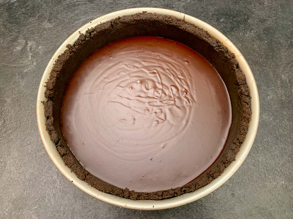 Fudge layer poured into the pan on top of the cheesecake crust.