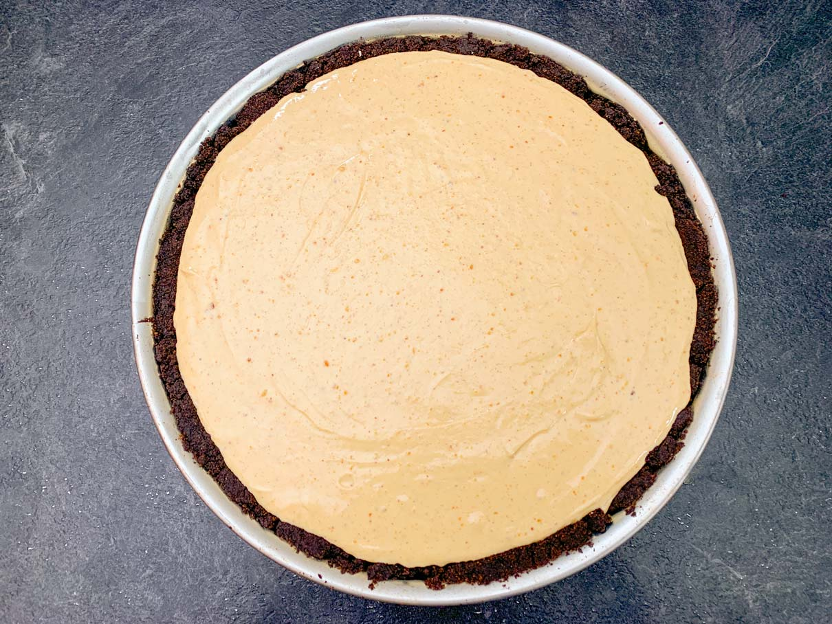 Cheesecake filling poured into the pan on top of the fudge crust