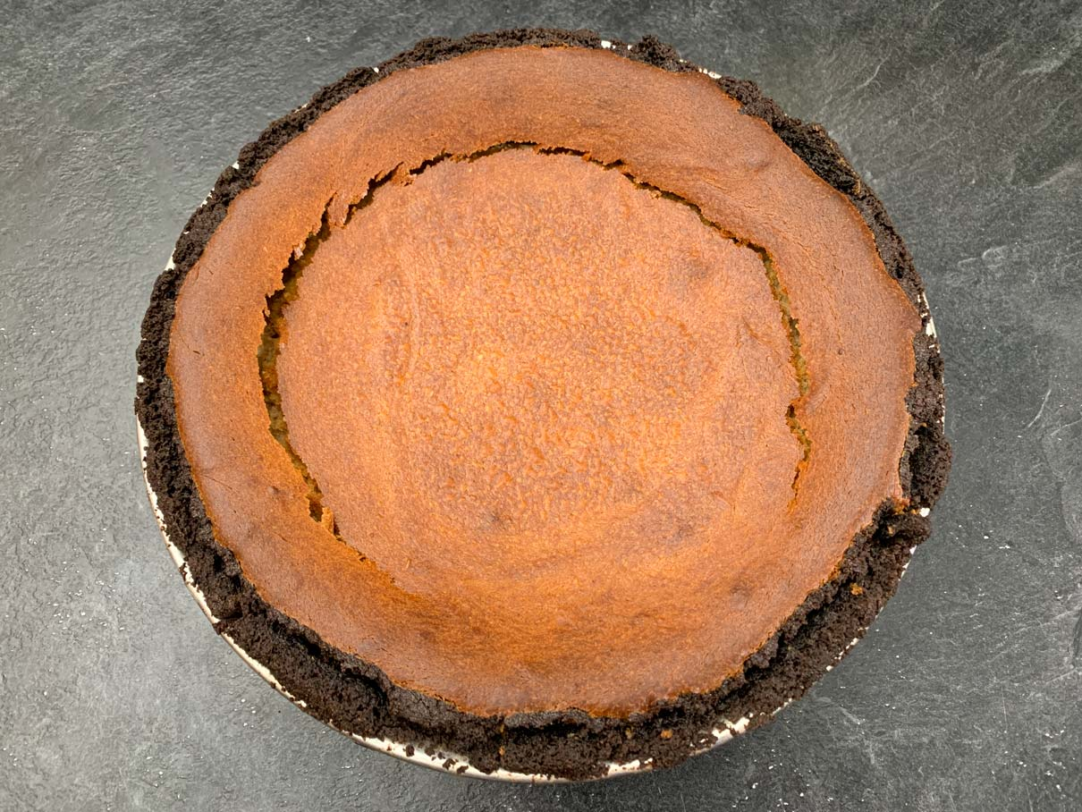 The cheesecake after it has cooled, with a large crack in it due to overbaking