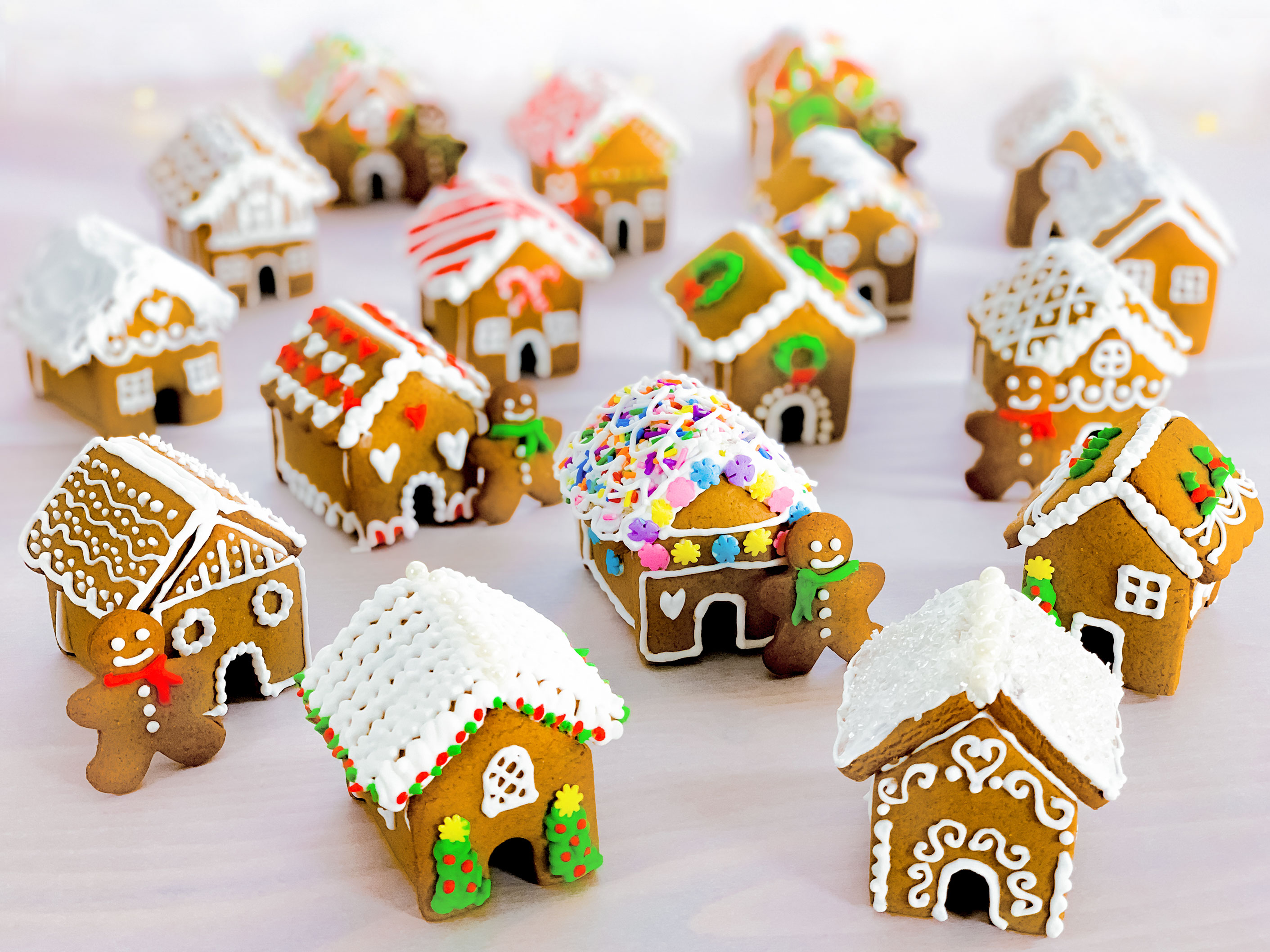 a group of mini gingerbread houses after they have been decorated, with some mini gingerbread men leaning against the houses