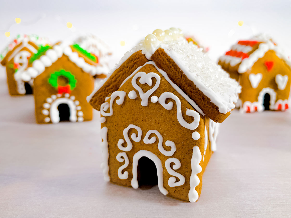close up of a mini gingerbread house, with white sugar sprinkles all over the roof