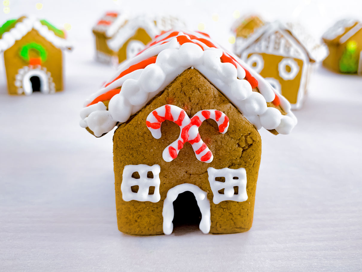 close up of a mini gingerbread house, with candy canes iced onto the front of the house