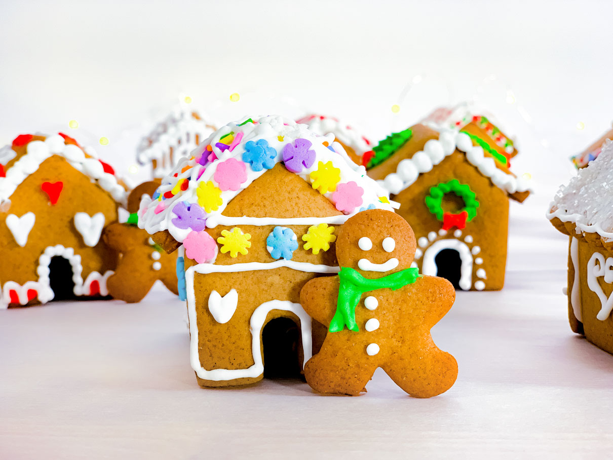 close up of a mini gingerbread house, with a sprinkle covered roof, and a little gingerbread man standing in front with a green scarf