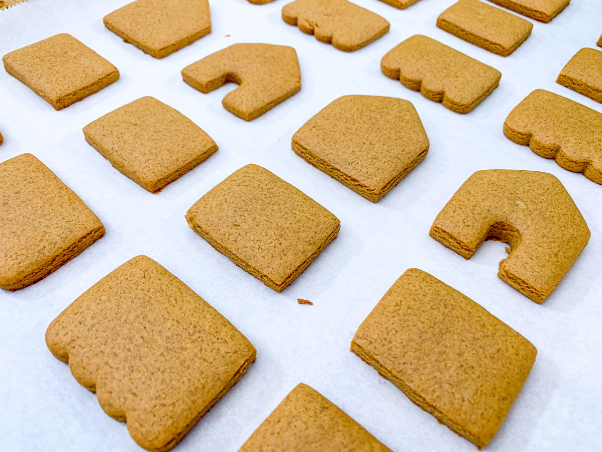 the baked gingerbread house pieces cooling on a cookie tray