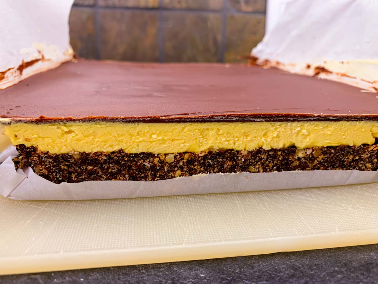 A side view of the Nanaimo bars, after the whole block has been lifted out from the pan