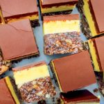Nanaimo bars all cut up, some facing upwards, some on their sides so you can see the layers