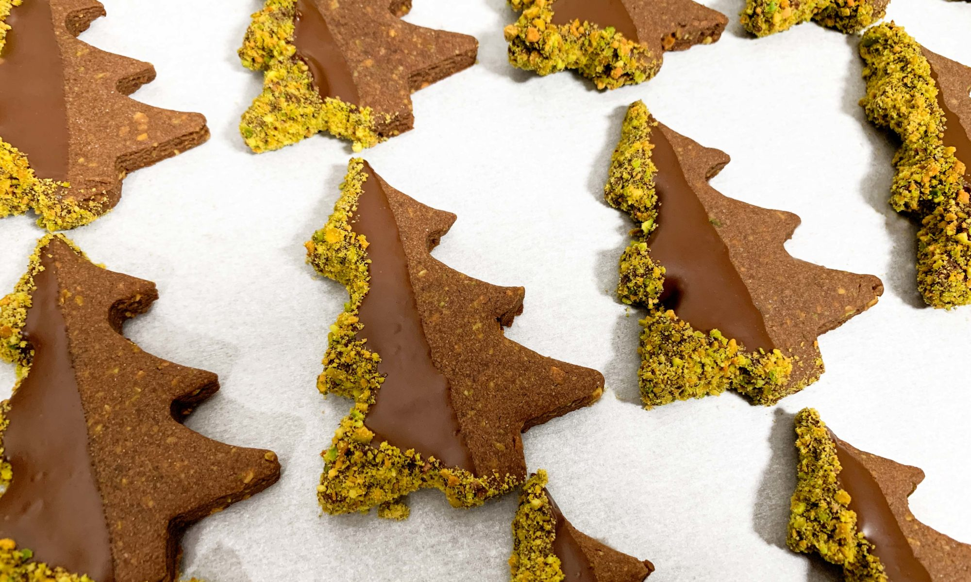 Tray of finished cookies, dipped in chocolate with pistachios crusted on the edges