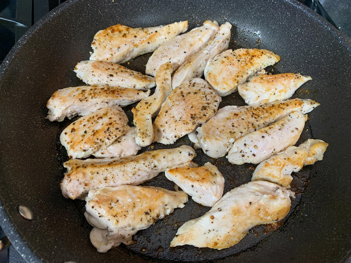 sliced chicken breast, cooked in a frying pan