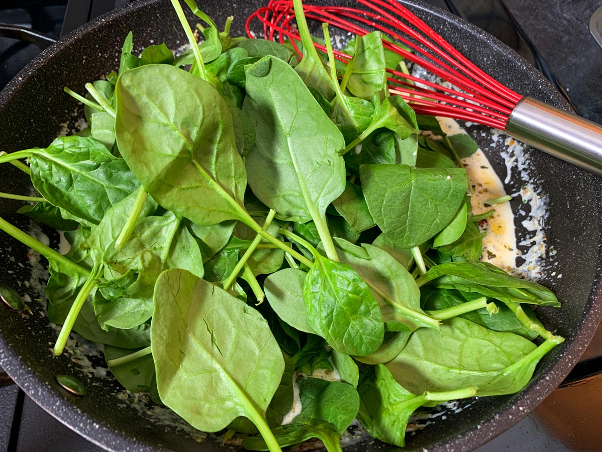 adding spinach and sun-dried tomatoes to the sauce