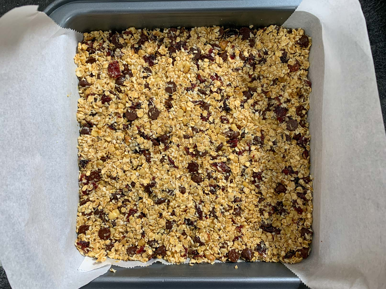 The granola bar mixture packed tightly into a pan