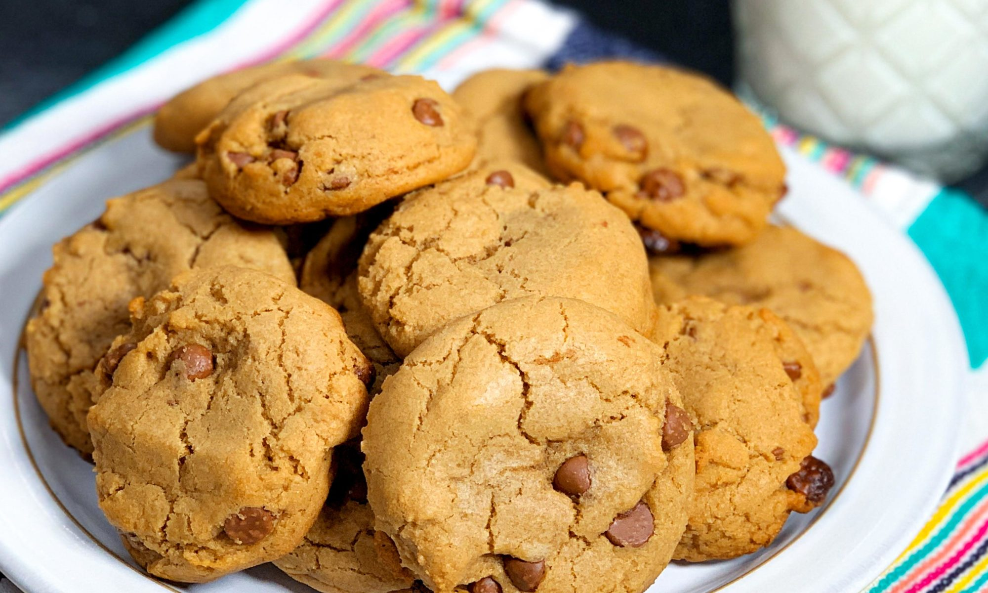 Close up of plate of cookies with glass of milk in the background